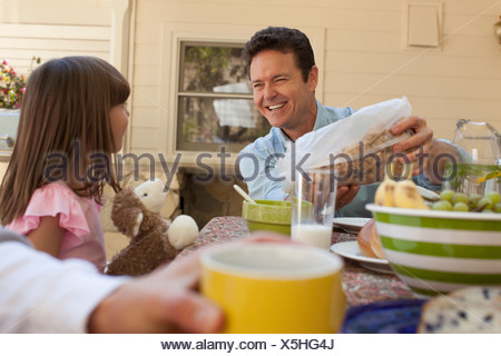 Father and daughter having breakfast outdoors - Stock Photo