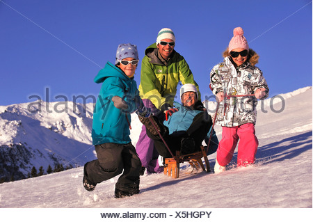 mother sitting on a sled having fun being pulled by her husband and her two sons, France - Stock Photo