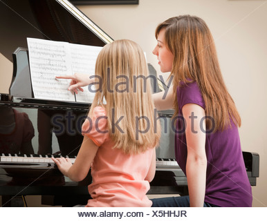 Girl (8-9) and mother playing grand piano - Stock Photo