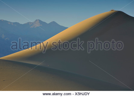 Tourists on Star Dune, the highest dune of the Mesquite Flat Sand Dunes, known from Star Wars, early morning light, Stovepipe - Stock Photo