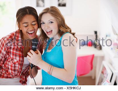 Teenage girls singing into microphone - Stock Photo