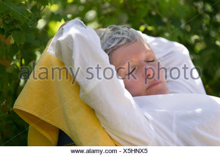 Senior woman sleeping on lounger - Stock Photo