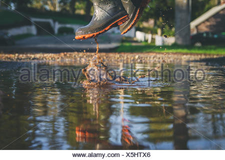 Low angle close-up of a boy jumping in a muddy puddle - Stock Photo