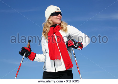 Young woman, about 25 years, wearing a bright jacket, a cap, dark sunglasses and a red scarf, against a blue sky - Stock Photo