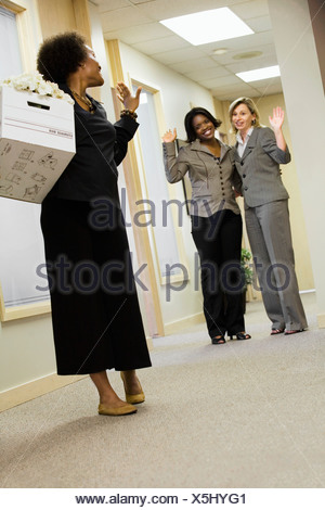 Businesswomen waving goodbye to a pregnant businesswoman in the office - Stock Photo