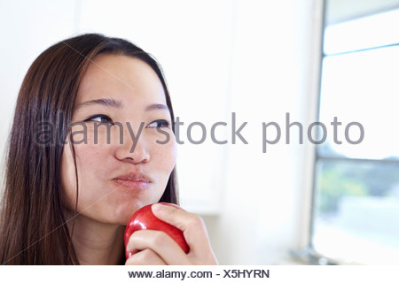 Young woman in kitchen eating red apple - Stock Photo