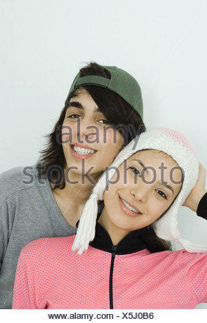 Young couple smiling at camera together, both wearing hats, cheek to cheek, portrait - Stock Photo