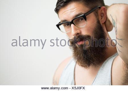 Portrait of brunette man with beard wearing eyeglasses - Stock Photo