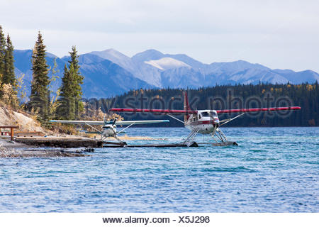 Floatplanes sit on Muncho Lake in Northern British Columbia, Canada. - Stock Photo