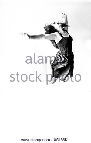 Smiling Young Woman Jumping Against White Background - Stock Photo