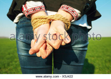 Female hands tied up with the rope - Stock Photo