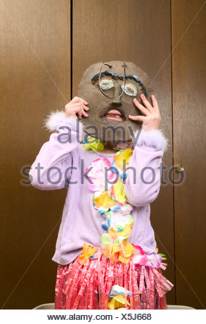 Young girl holding wooden mask over her face - Stock Photo