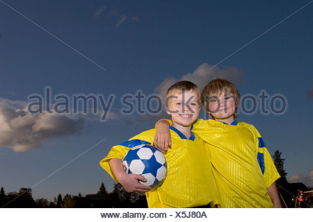 Portrait of two boys in soccer uniforms - Stock Photo