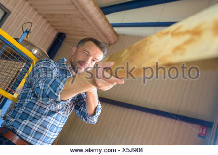 Man checking straightness of piece of wood - Stock Photo
