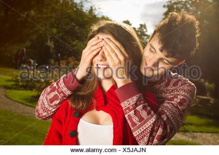 Man covering girlfriend's eyes in park