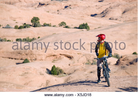 A mountain biker rests during a ride on the Slickrock Trail, Moab, UT. - Stock Photo