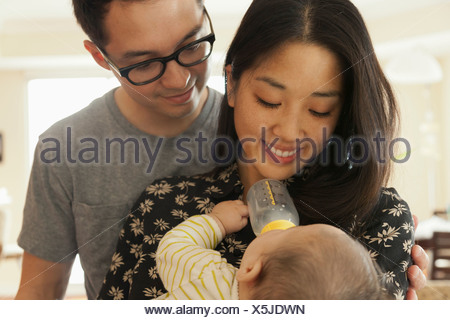 Mother feeding baby daughter whilst father watches - Stock Photo