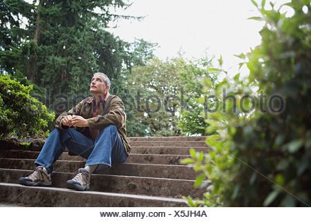 Man sitting on stone steps - Stock Photo