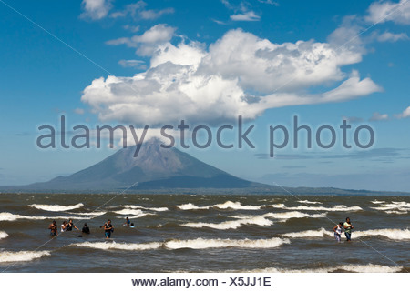 People walking on the shallow shore of Lago de Nicaragua, volcanic island of Ometepe and the stratovolcano Volcán Concepión at - Stock Photo
