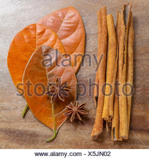 Still life of cinnamon sticks, anise cloves, and autumn leaves arranged on wooden surface - Stock Photo