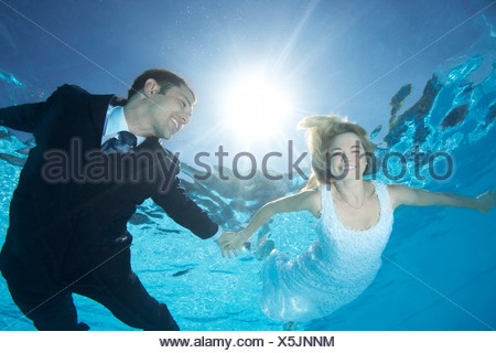 Bride and groom underwater - Stock Photo