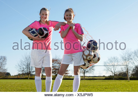 Football players carrying balls in field - Stock Photo