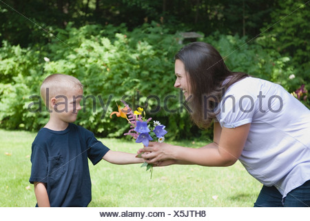 A little boy giving his mother flowers - Stock Photo