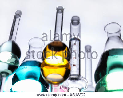 Beakers with liquids on reflective table - Stock Photo