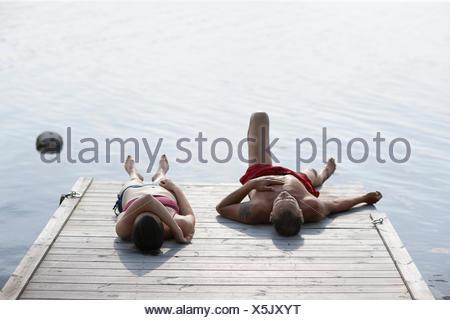 Sweden, Dalarna, Siljan, Man and woman lying on jetty - Stock Photo