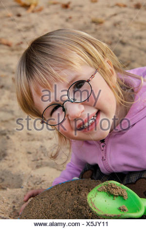 little girl playing in the sand, portrait of a child - Stock Photo