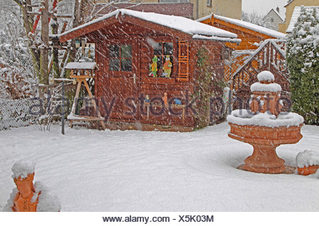 snow-covered garden with summer house in the driving snow, Germany - Stock Photo