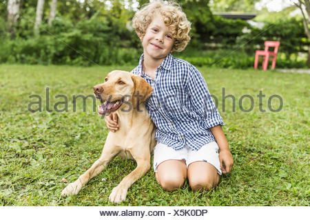 Portrait of boy sitting with dog in garden - Stock Photo