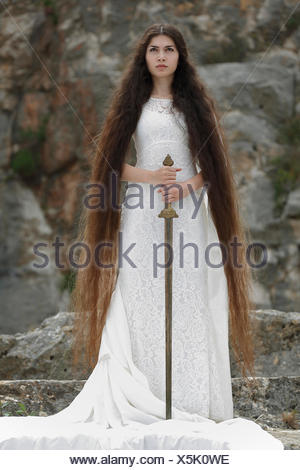 Reminiscence to Joan of Arc, Jeanne d'Arc, young woman in a white dress with a sword - Stock Photo
