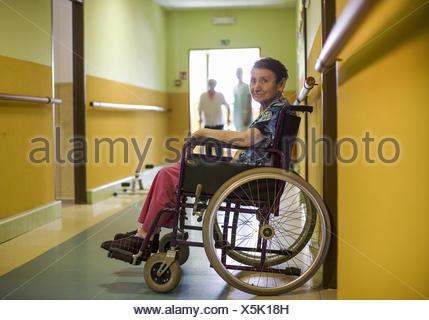 Altenheim, Seniorin sitzt am Gang in Rollstuhl (model-released) - Stock Photo