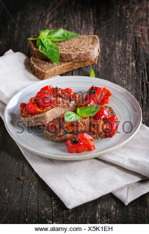 Italian tomato bruschetta with baked cherry tomatoes and fresh basil, served on gray ceramic plate with textile napkin over wood - Stock Photo