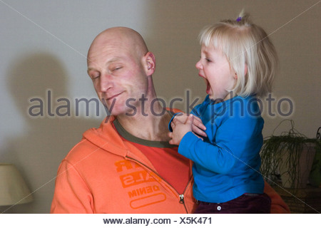Toddler throwing a tantrum and screaming loud while her father is giving in. - Stock Photo