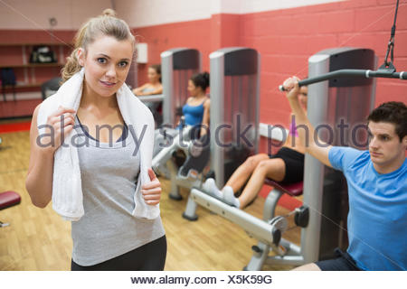 Smiling female trainer wearing towel around her neck - Stock Photo