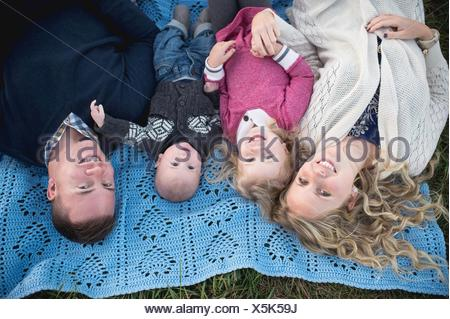 Overhead portrait of mid adult couple on picnic blanket with daughter and baby boy - Stock Photo