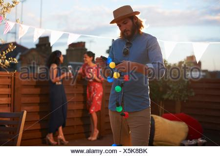 Man hanging garden lights for early evening party - Stock Photo