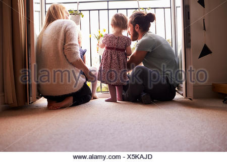 Family At Home Watering Plants On Balcony - Stock Photo