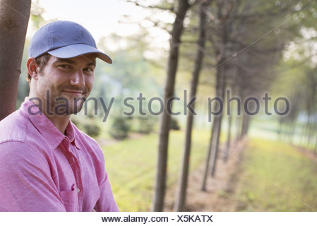 A man leaning against a tree looking at camera. - Stock Photo