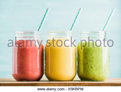 Freshly blended fruit smoothies of various colors and tastes in glass jars with blue straws. Green, yellow, red. Turquoise blue - Stock Photo
