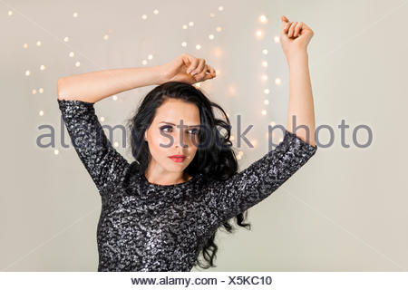 attraktive junge dunkelhaarige frau mit abendgarderobe am tanzen party feiertag glitzer kleid bokeh - Stock Photo
