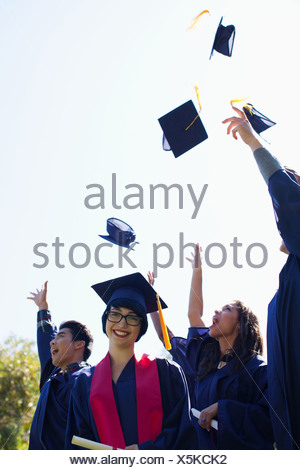 Graduates throwing caps in air outdoors - Stock Photo