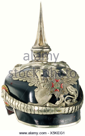 Baden: A helmet for aides-de-camp, of HRH the Grand Duke. The fibre skull has a slightly crazed surface, while the lacquer finish of the visor and neck guard is chipped in some places. The high, fluted spike can be screwed off. The large frontal plate bears the star of the House Order of Loyalty as its central device. Cambered chinscales are fastened to posts through officers' style cockades. The ribbed silk lining and sweatband show slight traces of wear. Size 55. Complete with storage case. An extremely rare helmet in a fine state of preservation. historic, h, - Stock Photo