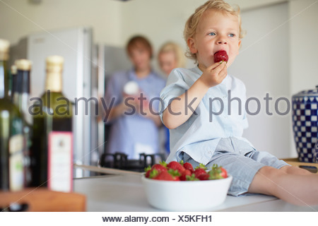 Boy eating strawberries on counter - Stock Photo