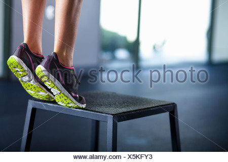 Young woman tiptoeing on edge of stool - Stock Photo