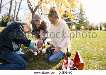Grandfather and grandchildren fixing model airplane in autumn park - Stock Photo