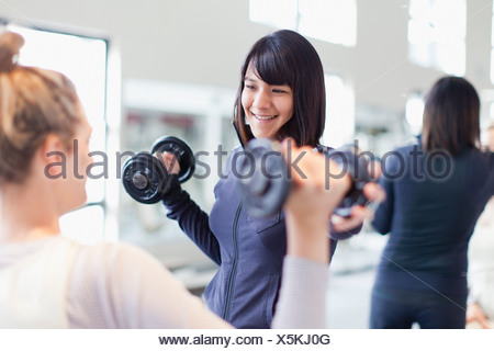 Trainer working with client in gym - Stock Photo