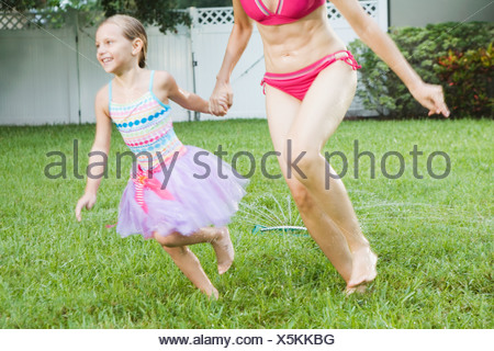 Mother and daughter running through sprinkler - Stock Photo